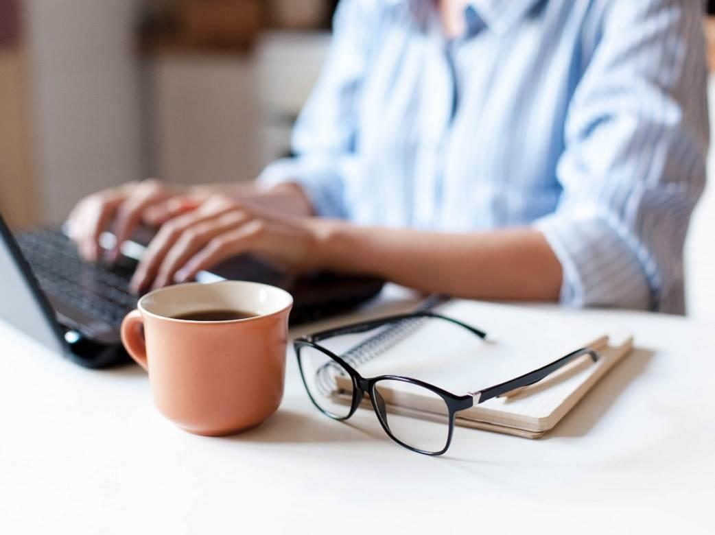 zena radi za laptopom sa soljom kafe i naocarima